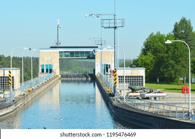 A lock is filled with blue water, with the lock gate closed. Some ducks are on the water. The control tower arches over the lock, and a truck is to one side. The sky is blue.