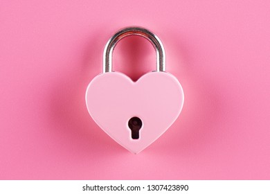 The lock in the form of a heart on a pink background
