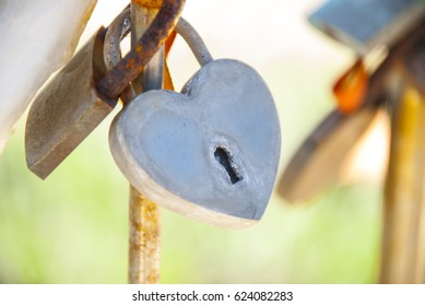The lock in the form of a heart is pinned on the bridge