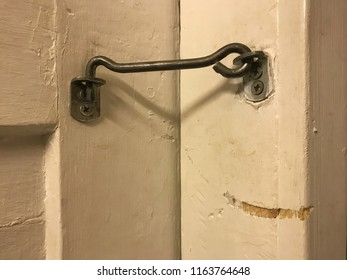 The lock hook on the old wooden door. The door is closed. On the doorpost there is a shabby hook. Background.
