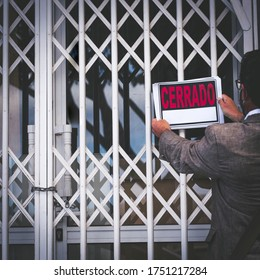 Lockdown and bankrupt economy crisis concept with unrecognizable store owner putting closed sign on the door - people and business coronavirus covid-19  emergency - cerrado is closed in spanish