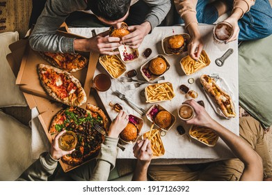 Lockdown fast food dinner from delivery service. Flat-lay of friends sitting and having beer quarantine party with burgers, french fries, sandwiches, pizza and salad over table background, top view - Shutterstock ID 1917126392