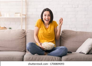 Lockdown leisure activities. Millennial girl laughing while watching funny movie at home