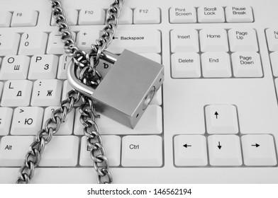 Locked chain on white computer keyboard