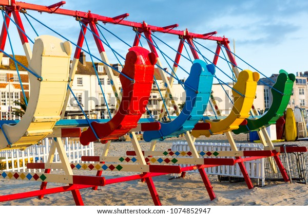 Locked colourful swings on Weymouth beach in sunrise light. Horizontal close up crop