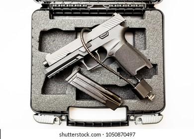 Locked disarmed secured handgun in case white background