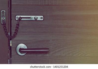 Locked doors. Old door latch. The locking mechanism on the old door. Close-up view of the door lock with a chain. Locked doors locked chain in closeup view.