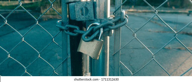 Locked Gate Tethered by metal chain and old rusty padlock on sunshines background. Wide photo.