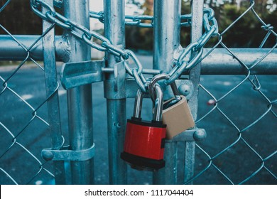 Locked Gate/Boarder Tethered by two metal chains (red and gold) and padlocks. Toned photo. Closed borders immigration concept.