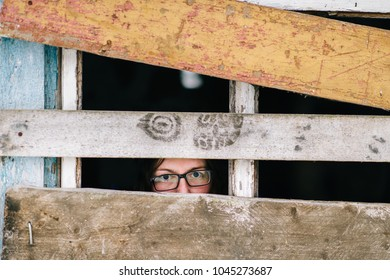 Locked up guilty girl in glasses emotional portrait. Woman slavery. Werid strange unusual person looking through slit in boarded up window in old wooden abandoned ghost house. Female eyes expression