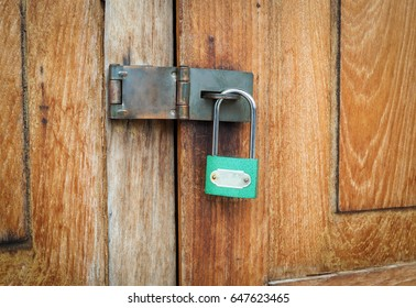 Locked padlock with chain at wooden door background, vintage