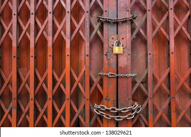 Locked rusty old red gate., Mean is Security