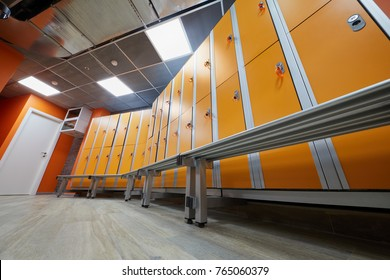 Locker room with rows of orange lockers at fitness center, low angle view.