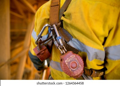 Locking carabiners which attached into red self retracting shock absorber safety device equipment are connecting into the top of fall arrest working at height safety body harness rescue loop
