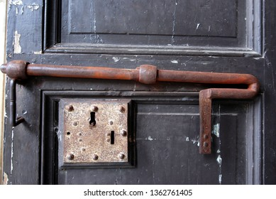 locks and large deadbolt closing an ancient wooden door