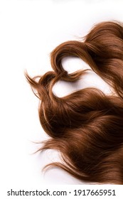 The locks of the red copper hair of the synthetic wig, shaped as a heart, isolated on the white background