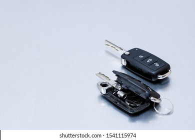 Locksmith broken or damaged car key fob and new remote vehicle key on aluminium background. Repair of broken or damaged remote key fob of any vehicle car service.- Image
