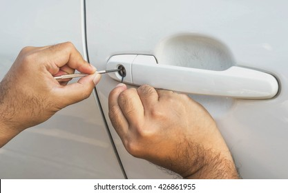 locksmith car will open white car door white screwdriver - selective to focus on key hold