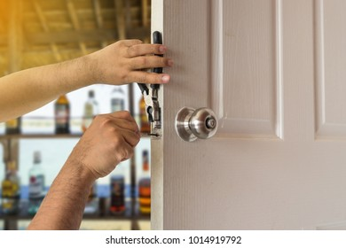 locksmith fix white wood door of bar alcohol with screwdriver and tool