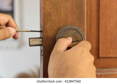 locksmith on wood door for repairing by screwdriver