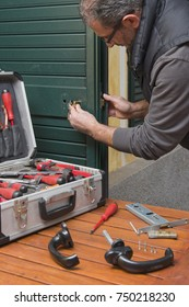 Locksmith repair the lock of a door of the house with a suitcase of tools.