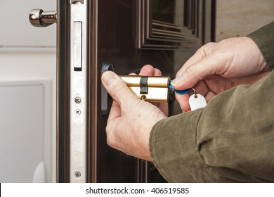 Locksmith repairing the lock on a house door