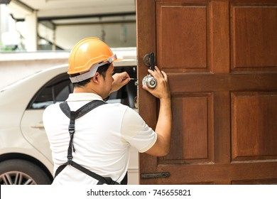 locksmith with safety helmet try to install knob on wood door for home service