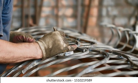 Locksmith at work in fitting shop, hands in gloves closeup. Master makes notes with a pencil on a metal bar measuring it applying to the finished metal fence. Art forging of metal products.