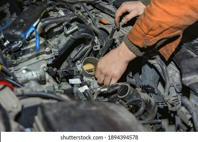 Locksmith-mechanic repairs a car in a car repair shop.