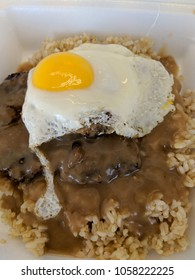 Loco Moco Close-up.  Loco Moco is a dish native to Hawaiian cuisine. There are many variations, this one consists of brown rice topped with hamburger patty, a egg over easy, onions and brown gravy.