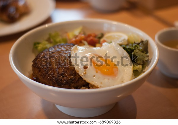 Loco moco is a meal in the contemporary cuisine of Hawaii. There are many variations, but the traditional loco moco consists of white rice, topped with a hamburger patty, a fried egg, and brown gravy.