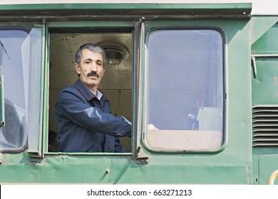 Locomotive engineer in the window of the cabin. Horizontal shot