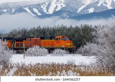 locomotive pulling train in winter close to Whitefish, Montana with Whitefish ski resort in background