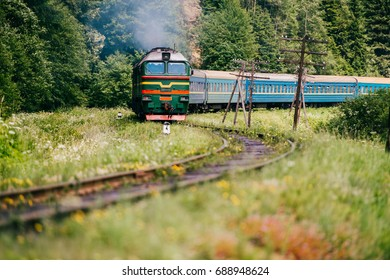 Locomotive with wagons riding railroad in carpathian mountains. People going to vacation. Train with passengers turning on railway. Travel and tourism in Ukraine. Time to rest. Reaching destination.
