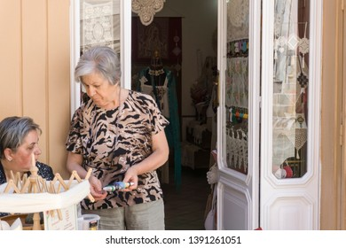 Locorotondo, Italy - 14 July 2018 - Women at house entrance in a street of The gorgeous white town in province of Bari, chosen among the top 10 most beautiful villages in Southern Italy