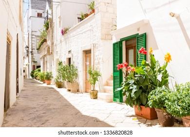 Locorotondo, Italy - August circa, 2016: Characteristic narrow streets with large pebble paving.