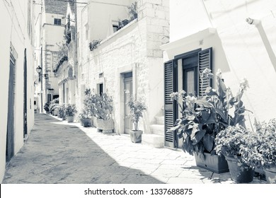 Locorotondo, Italy - August circa, 2016: narrow streets of the city, white house walls, street paving made of large stone pebbles, monochrome interpretation of colors.