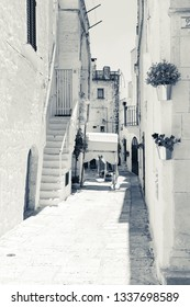 Locorotondo, Italy - August circa, 2016: House stairs between the streets of the city, white walls, decorative plants in front of the houses, street paving made of large stone pebbles, monochrome.