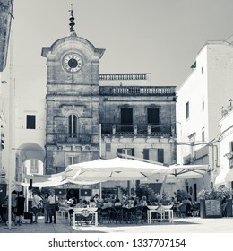 Locorotondo, Italy - July circa, 2017: The town's square frequented by tourists, people sitting under gazebos during the hot summer hours, facade of a historic building with clock tower, monochrome.