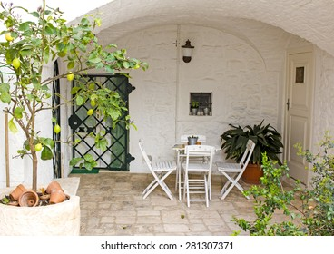 LOCOROTONDO, ITALY - MAY 2 : Cozy patio under a stone vault with potted plants and garden furniture in Locorotondo town, Apulia, southern Italy on May 2nd, 2015