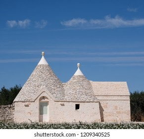 Locorotondo, Italy. September 2018. Traditional white-washed trulli house with conical roof, located outside the town of Locorotondo in the Itria Valley, Puglia, Southern Italy.