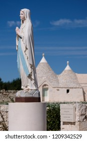 Locorotondo, Italy. September 2018. Traditional white-washed trulli house with conical roof, located outside the town of Locorotondo in, Puglia, Southern Italy. Statue of the Virgin in foreground.