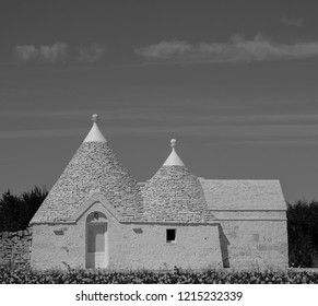 Locorotondo, Italy. September 2018. Traditional white-washed trulli house with conical roof, located outside Locorotondo in the Itria Valley, Puglia, Southern Italy. Photographed in monochrome.