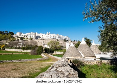 Locorotondo, Italy-March 24, 2019: City seen from below, is visible a dirt road in the countryside, you see on the right three rural buildings called Trulli.