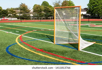 A locrosse goal with its game netting on a green turf field.