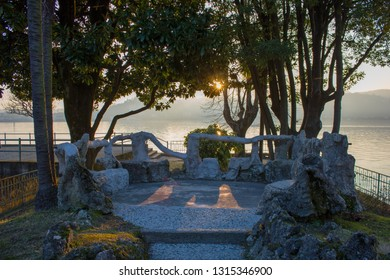 Locus Amoenus in Angera during the sunset light, Lago Maggiore, Italy 1/02/2019. Round terrace, with stone-marble chairs and trees, overlooking the Maggiore Lake.