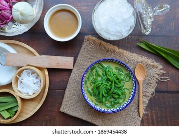 Lod Chong - Thai dessert of cendol pandan short vermicelli in palm sugar coconut milk on sackcloth of wood table - Top view with some ingredients