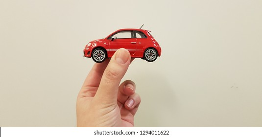 Lod, Israel - january 24 2019: red fiat 500 metal toy car holding in two fingers on white background