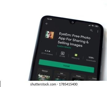Lod, Israel - July 8, 2020: EyeEm - Sharing & Selling Images app play store page on the display of a black mobile smartphone isolated on white background. Top view flat lay with copy space.