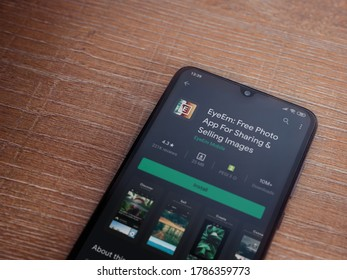 Lod, Israel - July 8, 2020: EyeEm - Sharing and Selling Images app play store page on the display of a black mobile smartphone on wooden background. Top view flat lay with copy space.